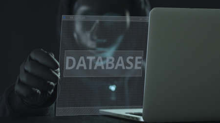 Unknown hacker wearing black mask pulls DATABASE tab from a laptop. Hacking concept Zdjęcie Seryjne