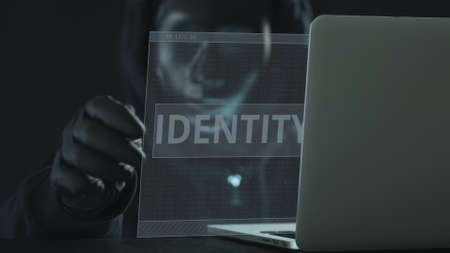 A hacker wearing black mask pulls IDENTITY tab from a laptop. Hacking concept