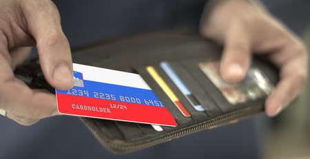 Man pulls plastic bank card with flag of Slovenia out of his wallet, fictional card number