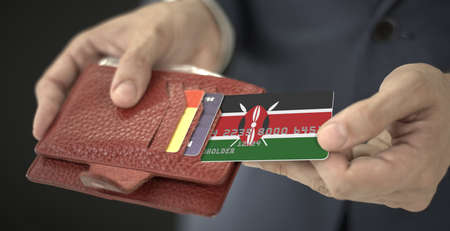 Pulling plastic bank card with flag of Kenia out of his wallet, fictional card number