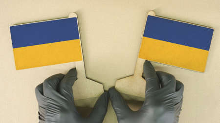 Flags of Ukraine made of recycled paper on the cardboard table