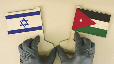 Flags of Israel and Jordan made of cardboard on the desk