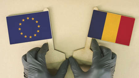 Flags of the European Union and Romania made of recycled paper on the cardboard table Stock Photo