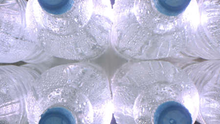 Top-down view of wet cold plastic bottles of mineral water Banque d'images