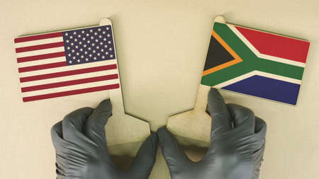 Flags of the USA and South Africa made of recycled paper on the cardboard table