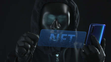 Hacker wearing dark mask pulls NFT of Non-Fungible Token text tab out of a smartphone. Modern blockchain technology concept