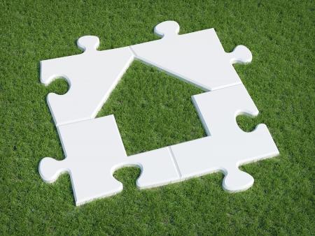 Puzzle house symbol on grass Standard-Bild