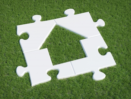 Puzzle house symbol on grass Stock Photo