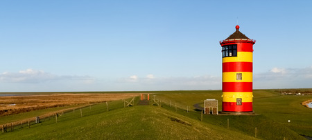 Pilsum, Germany - December 6, 2014: Lighthouse located near the coast especially for its colors in yellow and red stripes. It is located on a barrier of protection by the tides of the North Sea.