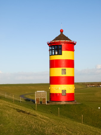 navigational light: Pilsum, Germany - December 6, 2014: Lighthouse located near the coast especially for its colors in yellow and red stripes. It is located on a barrier of protection by the tides of the North Sea.