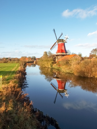 energy channels: Greetsiel, Germany - December 6, 2014: Traditional Windmill working and still used to grind. The second mill is currently under renovation due to a violent hurricane. Editorial