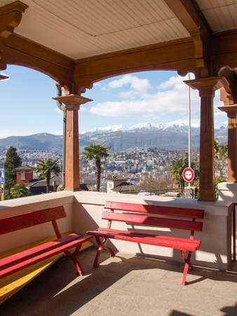 ber: Lugano, Switzerland - March 01, 2015: Benches Waiting at the station of the funicular Lugano. The red benches are typical for the Swiss tradition. The old wooden station is open and overlooks the bay of the city. Editorial