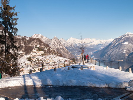 br: Monte Br?, Switzerland - February 22. 2015: Winter landscape from Monte Bre. view of the village of Br? with two tourists who observe the view from a panoramic terrace. Editorial