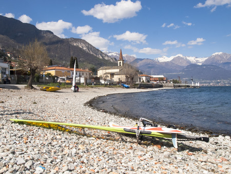 fun day: Pianello del Lario, Como - Italy - April 05, 2015: Windsurfer in a fun day of the Breva thermal wind typical of Lake Como during the spring  summer. The water temperature is slightly above the 10 degrees Celsius. The wind of around 1618 knots.