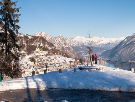 ber: Monte Br?, Switzerland - February 22. 2015: Winter landscape from Monte Bre. view of the village of Br? with two tourists who observe the view from a panoramic terrace. Editorial