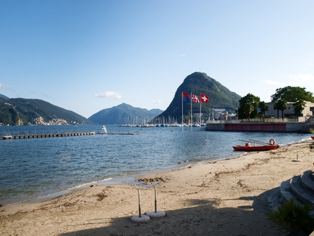national landmark: Lake Lugano, Switzerland: in the background the Monte San Salvatore and in the foreground the flags of Switzerland, Ticino, Lugano