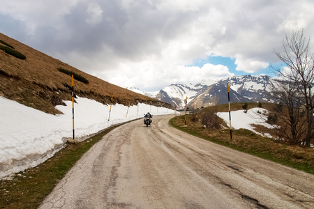 macerated: Italy, Apennines Umbria-Marche-Abruzzo - April 24, 2015: Road Trebbio, Bolognola, Sarnano. Panorama of the mountains Sibillini. Motorbike is going on the road during the photo shoot. Stock Photo