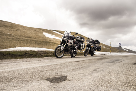 macerated: Italy, Apennines - April 24, 2015: Parked motorcycle located at the roadside at the passroad Trebbio, Bolognola, Sarnano. The road in winter is closed to traffic because of snow. Editorial