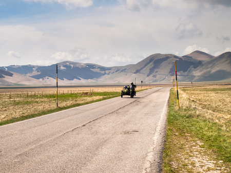 sidecar: Italy, Castelluccio di Norcia - April 25, 2015: Motorcyclists on the road of big plan of Monti Sibillini. Motorcyclists in a vehicle sidecar salute as they pass.