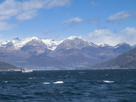 evocative: Lake of Como, Italy: Picture of the lake to the north with snow-capped mountains. The wind makes the evocative image.