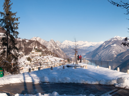br: Monte Br, Switzerland - February 22. 2015: Winter landscape from Monte Bre. view of the village of Br with two tourists who observe the view from a panoramic terrace. Editorial