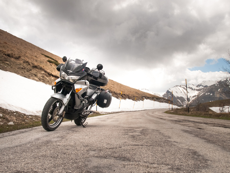 macerated: Italy, Apennines Umbria-Marche-Abruzzo - April 24, 2015: Road Trebbio, Bolognola, Sarnano. Panorama of the mountains Sibillini and motorbike parked on the road near the snow.