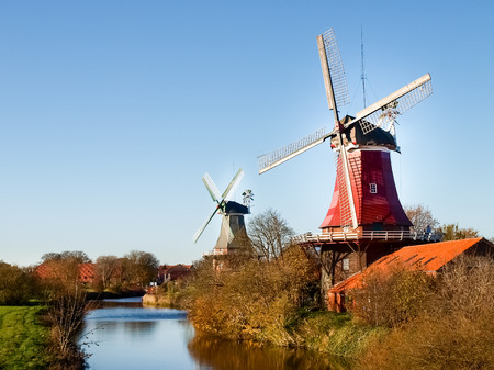 Greetsiel, Germany - November 4, 2011: Traditional Dutch windmills working and still used to grind. The green, western mill dates from 1856, the red, eastern mill was built in 1706. Publikacyjne