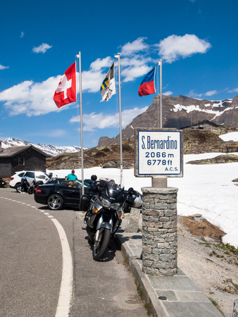 Bernardino: San Bernardino pass, Switzerland - May 14, 2015: Motorcycle parked near to each pass. This point is the top of the pass and many tourists taking pictures suggestive.