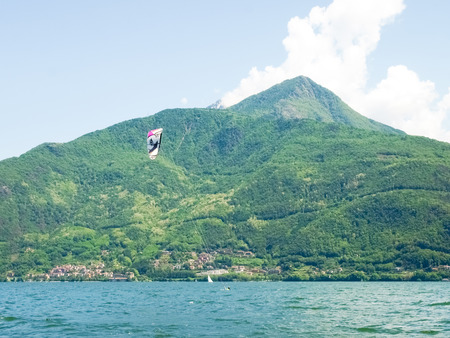 kiter: Pianello del ario, Italy - May 16, 2015: Kitesurfing action at the lake. Preparation, starting from the beach, sailing in the lake.