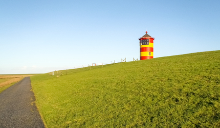navigational light: Lighthouse located near the coast especially for its colors in yellow and red stripes.