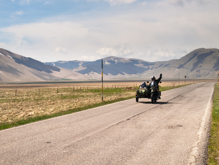 monti: Italy, Castelluccio di Norcia - April 25, 2015: Motorcyclists on the road of big plan of Monti Sibillini. Motorcyclists in a vehicle sidecar salute as they pass.