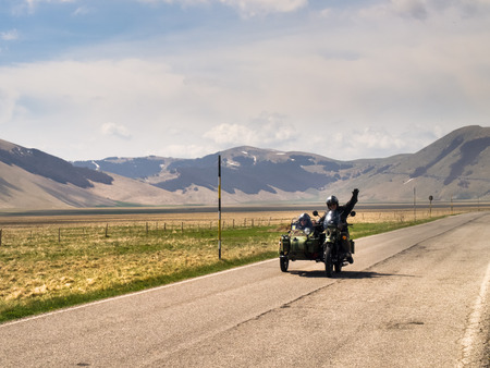 castelluccio di norcia: Italy, Castelluccio di Norcia - April 25, 2015: Motorcyclists on the road of big plan of Monti Sibillini. Motorcyclists in a vehicle sidecar salute as they pass.