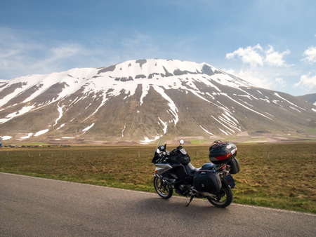 castelluccio di norcia: Italy, Castelluccio di Norcia  April 25, 2015: Motocicle parked on the big plan of Monti Sibillini. The motorcycle is located on the roadside overlooking the floor dedicated to the cultivation of lentils Editorial