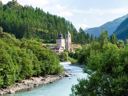 alp: Susch, Switzerland - July 12, 2015: Bell tower of the church tower near the river Inn
