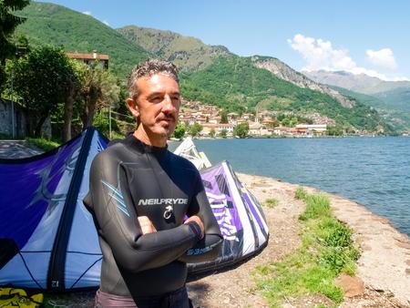 kiter: Pianello del Lario, Italy - May 16, 2015: Kitesurfing on the beach while preparing equipment Editorial
