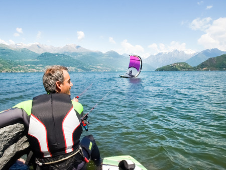kiter: Pianello del Lario, Italy - May 16, 2015: Kitesurfing action at the lake. Preparation, starting from the beach, sailing in the lake.