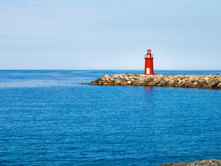 nautical structure: Oneglia, Italy - June 9, 2015: Red lighthouse at the port of entry reporting