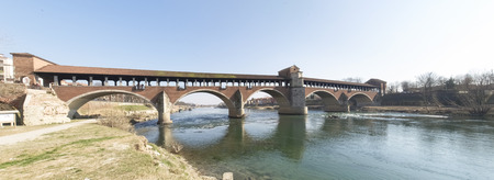 Pavia, Italy - March 8, 2015: Covered bridge over the river Ticino. Very quaint, has five arches and is completely covered with two portals at the ends and a small chapel religious center. Editorial