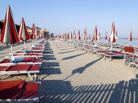 positioned: Diano Marina, Italy: Beach umbrellas positioned at regular file Stock Photo