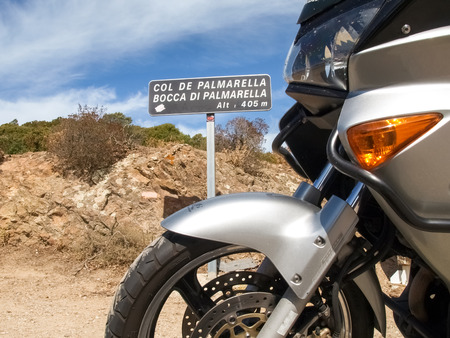 Corsica, France: Indicative signboard of Palmarella up with the motorcycle parked in front Stock Photo