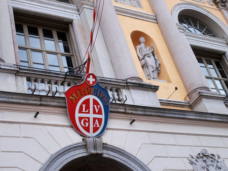 ticinese: Lugano, Switzerland - december 18, 2015: pennant of the city hanging on the facade of the town hall to the main square