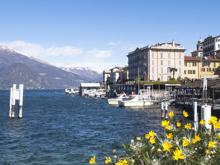 Bellagio lake of Como, Italy - April 1, 2015: Dock of Bellagio with nineteenth-century historic homes. The beautiful day is due to the wind from the north. Editorial