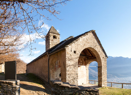 Sementina, Switzerland - december 9, 2016: Church of St. Bernard in the chestnut on Mornera. Ancient Romanesque church, in a tight angle but enriched with frescoes depicting the Madonna del Latte. Stock Photo