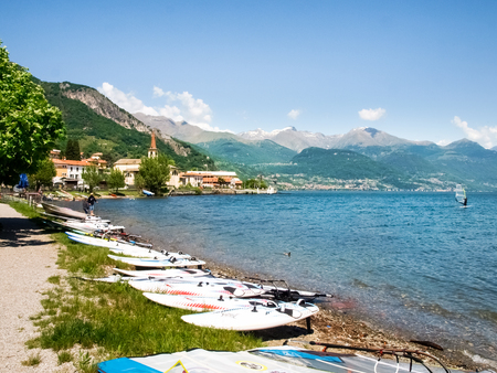 kiter: Pianello del Lario, Italy - May 16, 2015: Windsurf boards deposited on the beach by the lake, waiting to be used.