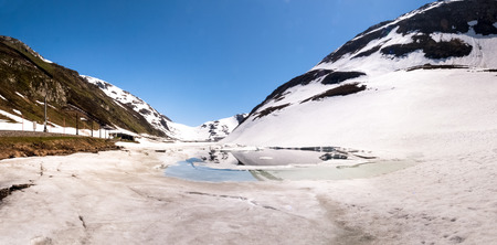 Oberalp pass, Switzerland : Artificial lake ice. The lake is illuminated by the sun during a beautiful day on the day of the Feast of the Ascension Stock Photo