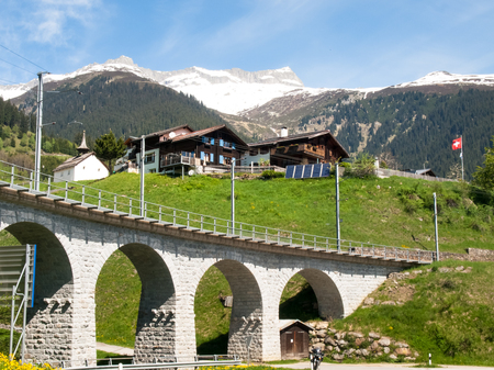 Surselva, Switzerland - May 14, 2015: Bridge of the Rhaetian Railway in the Surselva valley. The deck is illuminated by the sun during a beautiful day on the day of the Feast of the Ascension. Stock Photo