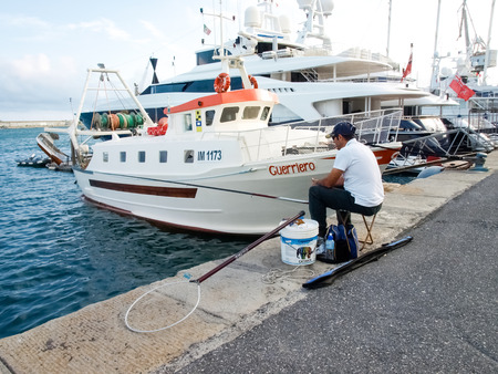 Oneglia, Italy - June 14, 2015: Fisherman sitting at the port fishing among the moored boats