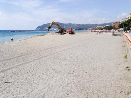 San Bartolomeo, Italy - June 16, 2015: Construction machines work on the beach machines Publikacyjne