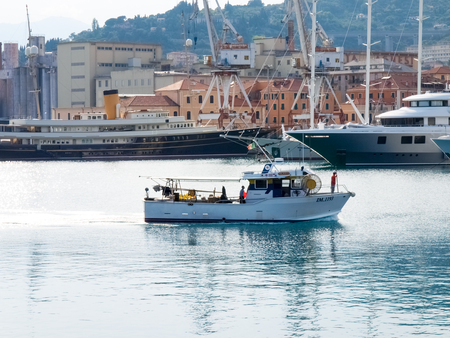 Oneglia, Italy - June 9, 2015: Marina and fishing. Several fishing boats are moored. In the background the buildings typical of Oneglia.