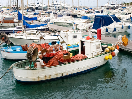 Oneglia, Italy - June 12, 2015: Fisherman system networks on the small boat moored in the harbor Publikacyjne